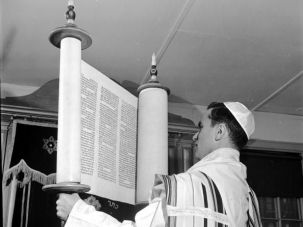 Truths and Contradictions: A rabbi lifts the Torah to show it to his congregation