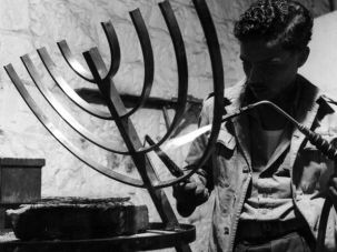 In the Line of Fire: A young man making a menorah at the Bezalel School of Arts and Crafts in Jerusalem, circa 1950.
