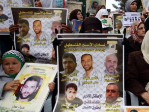 Palestinians holding placards and photographs depicting Palestinian prisoners held in Israeli jails during a protest.
