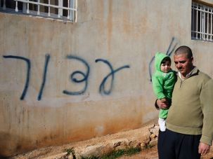 Palestinian Hussein al-Najjar Darwish holds his nine-month-old son as he stands in front of his house sprayed with graffiti reading in Hebrew: 'revenge' and 'hello from the prisoners of Zion', in the village of Beitillu, near Ramallah in the Israeli occupied West Bank on December 22, 2015. Two tear gas canisters were also thrown into the Palestinian home by suspected Jewish extremists, Israeli police said, but the family there at the time was not hurt.