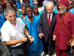 Acceptence: Israeli President Shimon Peres (center) holds hands with Black Hebrews leader Ben Ammi Ben-Israel (in red) at an event at the group?s Village of Peace in Dimona, where Peres celebrated his 85th birthday in August.