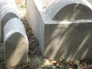 A small tombstone containing a child next to an adult tombstone at Calcutta?s Jewish Cemetery. (Photograph by Robert Hirschfield)