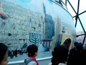Virtual Tourists: Visitors to the Israel pavilion walk past a mural depicting the Western Wall.