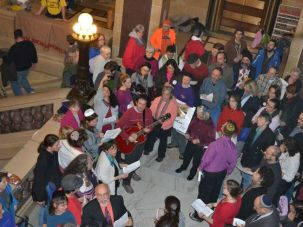 Shabbat in the Capitol: Jews protesting on behalf of public sector workers in Madison, Wis., gather for evening services Friday, February 25. Playing guitar and leading them in song is Aviv Kammay, center.