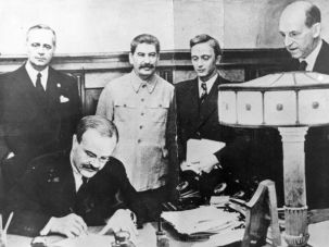 The Fire is Stoked on August 23, 1939: Vyacheslav Molotov, Russian foreign minister, signs a non-aggression pact that was negotiated between Soviet Russia and Germany at the Kremlin in Moscow. Standing behind him is his German counterpart, Joachim von Ribbentrop (left), and Joseph Stalin (center).