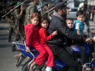 Trapped:  A Palestinian man rides a motorcycle with his children past masked militants of Ezzedine al-Qassam Brigades, Hamas?s armed wing, as they parade in Jabalia refugee camp, northern Gaza Strip, on November 14 during an anti-Israel march.