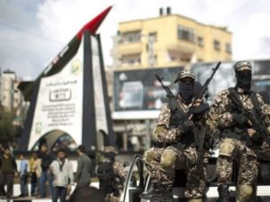 Unequivocally Bad Guys: Palestinian militants of the Ezzedine al-Qassam Brigades, Hamas's armed wing, sit on a pick-up truck in front of a model of a Gaza Strip made M75 rocket newly displayed at the al-Jalaa square on March 10 in Gaza City