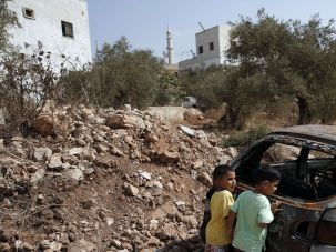 Palestinian children inspect the remains of their car after alleged Jewish settlers daubed the family home with Hebrew graffiti, which reads 'vengeance, Henkin.'
