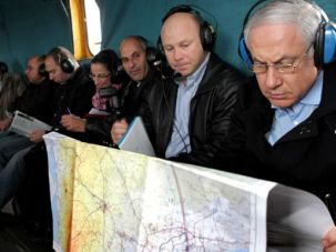 Mapping It: Israeli Prime Minister Benjamin Netanyahu studies a map while aboard a military helicopter heading toward Israel?s southern border with Egypt on January 21. Netanyahu has ordered construction of the barrier along Israel?s 155-mile desert frontier.