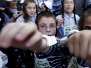 Another World: Ultra-Orthodox Jewish children wear handcuffs as they protest Israel's draft law.