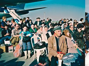 Ingathering: (Clockwise from left) Immigrants from the Soviet Union arrive in Israel in 1990, French immigrants disembark in 2005, a Yemeni immigrant blows a shofar at an Ashkelon absorption center in 1993, and an Ethiopian woman kisses the ground at Ben-Gurion International Airport in 1990.