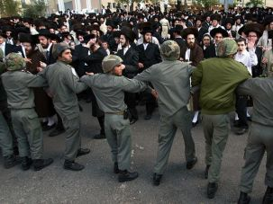 Day of Unrest: Israeli police create a barrier in front of 2,000 ultra-Orthodox protesters who demonstrated outside one of Intel?s plants in Jerusalem on November 21. They were protesting the company?s decision to operate on Saturdays.