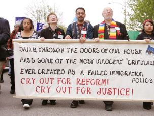 Holding up: Former workers at Agriprocessors (far left and right), march with Father Paul Ouderkirk (second from right), the priest at St. Bridget?s Catholic Church in Postville, Iowa, during an event earlier this year marking the one-year anniversary of the Postville immigration raid.