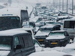 Cars remained stranded in the snow on a highway to Jerusalem.