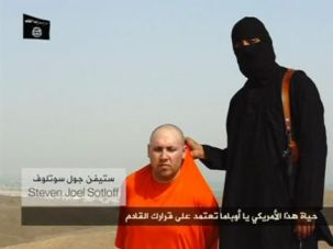A masked Islamic State militant speaks next to U.S. journalist Steven Sotloff in this still image from a video authenticated by the White House.