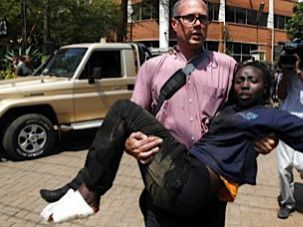 Journalist Tom Kirkwood rescuing a woman injured in a shootout between armed men and the police at the Westgate shopping mall in Nairobi, September 21, 2013.