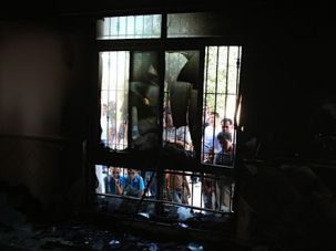 Attacks: Palestinians from the village of Jabaa, east of Ramallah, look through broken glass inside a mosque which settlers tried to burn last summer.