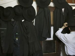 Making a Living:  A yeshiva student puts on a black hat in Bnei Brak. Unlike their cousins in the U.S., few Israeli ultra-Orthodox work, resulting in a crushing poverty rate of 66%.