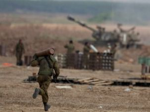 Running For Their Lives: An Israeli soldier runs with shell next to artillery cannons at the Israeli-Gaza border.