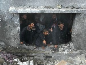 Deadly Strike: Palestinians search through rubble of Gaza building after Israeli strike that killed 12, including 10 members of one family.