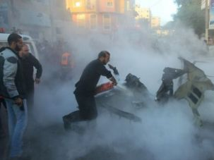Hell on Earth: Palestinian emergency workers douse flames after Israel strikes Hamas targets.