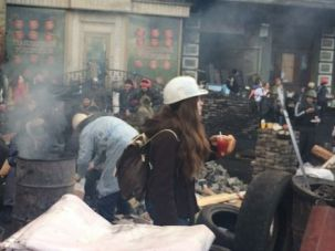 Mission of Mercy: Alena Druzhynina of the American Jewish Joint Distribution Committee, pictured above in white helmet, entered the tense Independence Square area of Kiev to bring food to a trapped retiree.