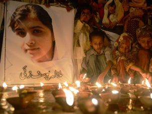 Pakistani children place oil lamps next to a photograph of child activist Malala Yousafzai, who was shot in the head in a Taliban assassination attempt.