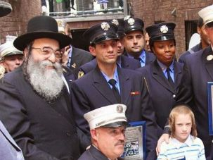Doomed Hero: New York Fire Lt. Gordon Ambelas, second from right, is honored for helping rescue 7-year-old Mendy Gotlieb, front, in a May accident. Ambelas was tragically killed in a high-rise blaze last weekend.