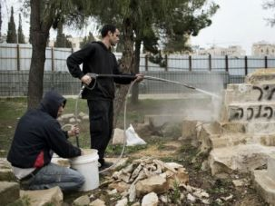 Shameful Scrawl: Workers remove spraypaint after Jewish extremists painted anti-Arab graffiti on a Muslim cemetery in Jerusalem.