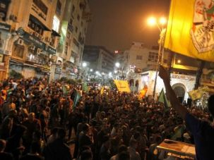Captive Audience: Crowds gather in streets of Ramallah to cheer reports that Hamas fighters captured an Israeli soldier in Gaza.