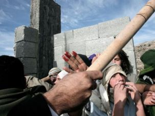 Set Upon: The stick of a Palestinian man is seen as Palestinans from the West Bank village of Qusra beat and detain a group of Israeli settlers at a construction site.