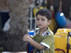 Need a Drop To Drink: Palestinian boy waits to collect water during brief humanitarian truce in Gaza.
