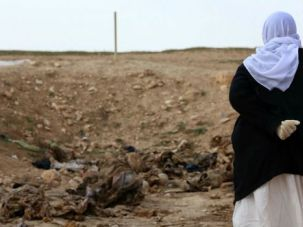 A woman from Iraq's Yazidi minority walks through an area strewn with bones of suspected victims of Islamic State massacres.
