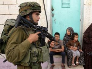 #BringBackOurBoys: Israeli soldier confronts a Palestinian family in a village near Hebron as the search continues for 3 kidnapped teenagers.