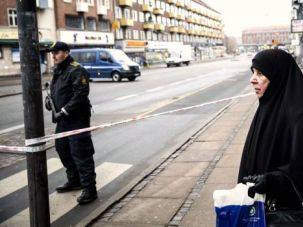 On High Alert: A veiled woman passes by a police officer surveying a street near the site of the Copenhagen shooting.