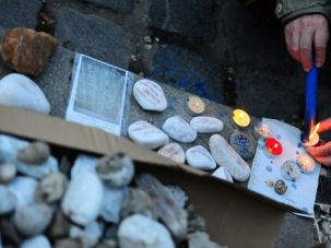 Stones of Memory: An elderly man lights a candle on the Szabadsag square, where Hungarian government's plans to build up a memorial site which critics say symbolises a whitewashing of the state's role in the Holocaust.
