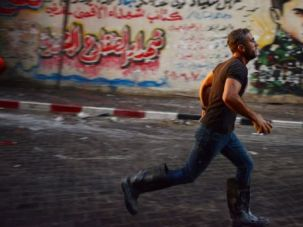Run for Help: Palestinian firefighter runs to douse a blaze at a soap factory struck by Israeli air strikes before a truce went into effect.