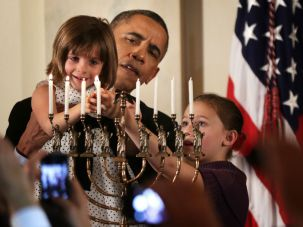 President Obama lights the menorah during the White House's 2014 Hanukkah celebration.