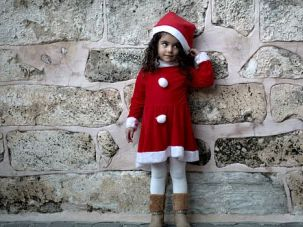 Gaza Christmas: Palestinian girl waits to attend church in Gaza city as preparations for holiday shift into gear across the Holy Land.
