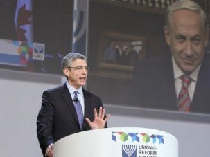 Speaking to Flock: Rabbi Rick Jacobs addresses the Union for Reform Judaism?s biennial conference, as Israeli Prime Minister Benjamin Netanyahu appeared on a big screen video link.