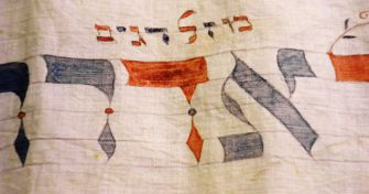 Sacred Sashes: Wimpels were used for Torah wrapping and bris swaddling. The top two words are Mazel Dagim (lucky fishes). The bigger word is Adar. Same astrology signs apply so this is Pisces.