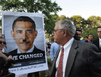 Sign of the Times: Rep. Barney Frank looks at a sign held by followers of fringe figure Lyndon LaRouche comparing President Obama to Hitler outside an August 18 town hall meeting.
