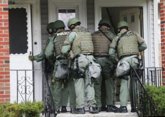 SWAT team members go door-to-door searching for 19-year-old Boston Marathon bombing suspect Dzhokhar A. Tsarnaev on April 19, 2013 in Watertown, Massachusetts.