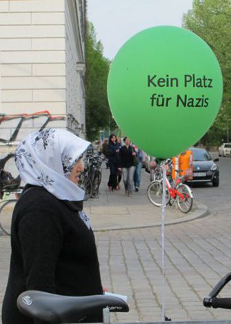 The Green Menace?: A Turkish woman stands alongside an anti-fascist message on May Day in Berlin?s Kreuzberg section.