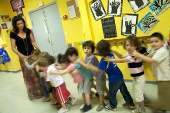En Route: A teacher from EJAP?s all-female staff leads a conga line of kindergartners to lunch.