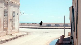 A woman sits on a wall in the seaside suburb of La Goulette, which once had a large Jewish community.