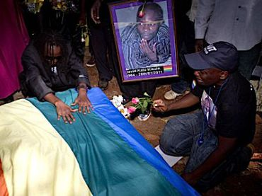 At the funeral of murdered activist David Kato, mourners pay their respects.