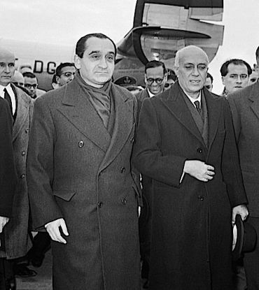 Statesmen Pierre Mendès France welcomes Jawaharlal Nehru at a French airfield.