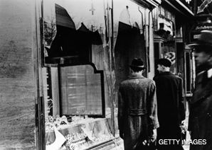 Just Passing By: Onlookers examine a destroyed Jewish shop window, November 10, 1938, the day after Kristallnacht.