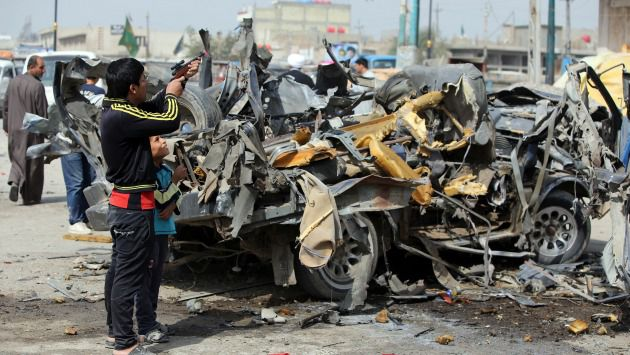 Boy aims toy gun at wreckage of a Baghdad car bombing, one of 9 across Iraq that killed 14 on March 5. And that wasn?t Iraq?s worst day in March.